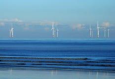 Zee kustwindfarm in een kalme blauwe overzees royalty-vrije stock afbeelding