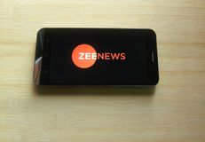 Zee News app. On smartphone kept on wooden table royalty free stock photo