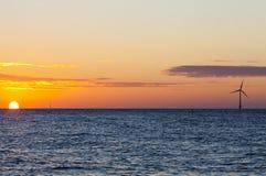 Zee windturbine bij zonsopgang Stock Foto