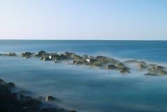 """Zeegezicht†""""Lange blootstelling van tropische overzeese golven die kustlijnrotsen raken Stock Foto's"""