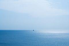 Zeegezicht en een varende boot stock fotografie