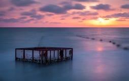 Zeegezicht en Lege Kooi bij Kleurrijke Zonsondergang stock afbeelding