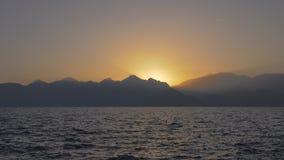 Zeegezicht met bergen en zonsondergang stock footage