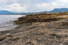 Zeegezicht met een rotsachtige kustlijn onder een blauwe hemel stock afbeelding