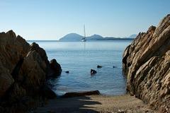 Zeegezicht met een vastgelegde varende boot en een strand met grote rotsen stock afbeeldingen