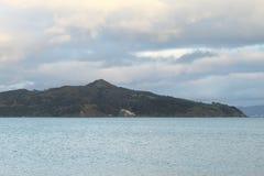 Zeegezicht met eiland op horizon in de avond Stock Foto
