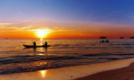 Zeegezicht met kayakers bij zonsondergang Royalty-vrije Stock Afbeelding
