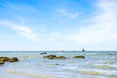 Zeegezicht met rotsen in de voorgrond en de bewolkte blauwe hemel met a Stock Foto's