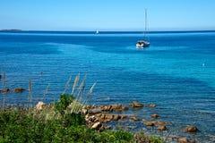 Zeegezicht met sommige installaties en rotsen op het strand en een varende boot stock foto
