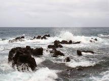 Zeegezicht met stormachtige dramatische golven die over kustrotsen met witte branding breken stock fotografie