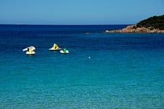 Zeegezicht met wat pedalos en boten het drijven stock afbeelding