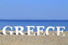 Zeegezicht met wit woord Griekenland Stock Foto