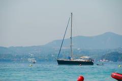 Zeegezicht met zeilboot de achtergrond van de blauwe hemel en de bergen Ontspan en reis concept yachting Boot die binnen varen royalty-vrije stock foto's