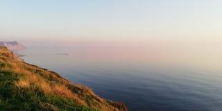 Zeegezicht Schitterende roze en lilac zonsondergang over de stille uitgestrektheid van het overzees royalty-vrije stock afbeelding