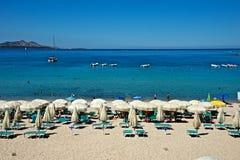 Zeegezicht van een zandig strand met ligstoelen en strandparaplu's Stock Foto's