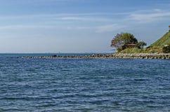 Zeegezicht van pijler voor visserij in de Zwarte Zee met larus, plattelandshuisje en boom bij kust, oude stad Nessebar stock afbeeldingen