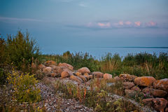 Zeegezichtmening Rotsachtig strand in avond Kiezelsteenkust Gekleurde foto Stock Foto