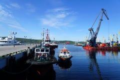 Zeehavenkraan en sleepboten aan de pijler wordt gesleept die royalty-vrije stock foto's