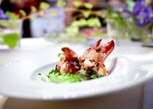 Zeekreeftschotel in restaurant met lijst en bloemstuk wordt voorbereid dat royalty-vrije stock fotografie