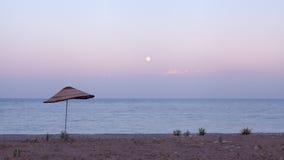 Zeekust met een paraplu van de zon bij zonsondergang in Turkije Stock Foto