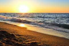Zeekust op een achtergrond van de het toenemen zon stock afbeelding