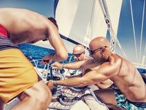 Zeelieden die aan zeilboot werken stock fotografie