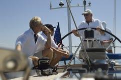 Zeelieden die bij het Roer op een Jacht spreken stock fotografie