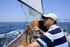 Zeeman die in het overzees vaart. Zeilboot over blauw Stock Foto's