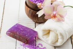 Zeep, handdoek en bloemensneeuwklokjes Bloemen, overzees zout en handdoek op witte houten backgr Royalty-vrije Stock Afbeelding