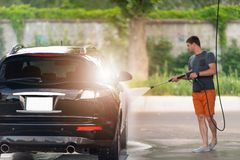Zeepsop van de jonge mensen het hosing zeep van zijn auto stock afbeeldingen