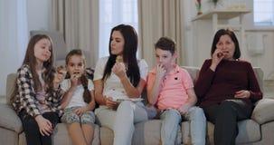 Zeer aantrekkelijke moeder met haar jonge geitjes en een oma die koekjes eten terwijl binnen het letten van op een TV voor de cam stock videobeelden