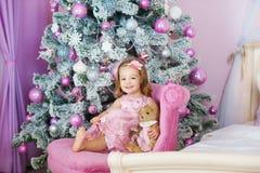 Zeer aardig charmant meisjeblonde in roze kledingszitting op een kind` s leunstoel en lach luid de achtergrond van Stock Afbeelding