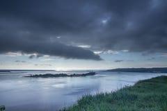 Zeer bewolkt weer Zwarte wolken over de rivier De rand van de rivierbank landschappen Royalty-vrije Stock Afbeelding
