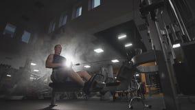Zeer bodybuilder van de machts voert de atletische kerel oefening met gymnastiekapparaten binnenuit stock video