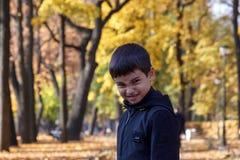 Zeer boos weinig jongen die camera op de achtergrond van het de herfstpark onder gele bladeren bekijken royalty-vrije stock foto