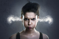 Zeer boze vrouw met rook die uit haar oren komen stock foto