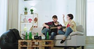 Zeer charismatische dame met een kerel die op een gitaar op de bank in een ruime woonkamer zingen terwijl het zitten op de bank stock footage