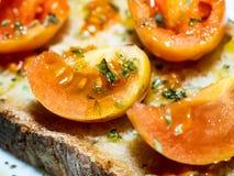 Zeer close-upschot van een geroosterde Italiaanse broodbruschetta met verse tomaten, olijfolie stock fotografie
