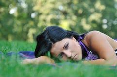 Zeer droevig - jonge vrouw in gras Stock Afbeelding