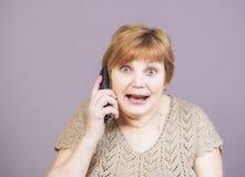 Zeer emotionele vrouw met gouden tanden met de telefoonzaktelefoon op een grijze achtergrond Royalty-vrije Stock Fotografie