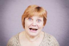 Zeer emotionele vrouw met gouden tanden op een grijze achtergrond Stock Fotografie