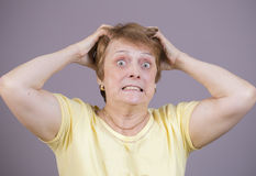 Zeer emotionele vrouw op een grijze achtergrond Royalty-vrije Stock Foto's