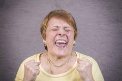 Zeer emotionele vrouwenschreeuwen op een grijze achtergrond Stock Afbeelding