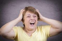 Zeer emotionele vrouwenschreeuwen in zorg op een grijze achtergrond Stock Afbeelding