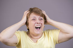 Zeer emotionele vrouwenschreeuwen in zorg op een grijze achtergrond Royalty-vrije Stock Foto