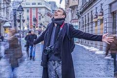 Zeer gelukkige fotograaf die met zijn die wapens glimlachen wijd in de hoofdstraat van Belgrado worden uitgespreid stock foto's