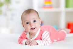 Zeer gelukkige lachende baby in roze kleren die op zijn buik liggen Zuigeling die recht de camera bekijken royalty-vrije stock fotografie