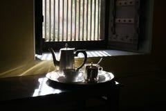 Zeer glanst het Goedemorgentheestel met glanzende zilveren werktuigen, Ochtendzonsopgang lichte komst door venster op het tafelzi Royalty-vrije Stock Fotografie