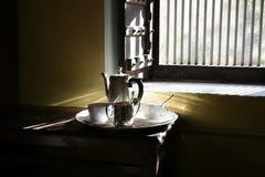 Zeer glanst het Goedemorgentheestel met glanzende zilveren werktuigen, Ochtendzonsopgang lichte komst door venster op het tafelzi Stock Foto