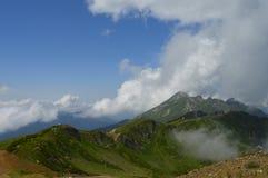 Zeer grote bergen met wolken, mist en blauwe hemel royalty-vrije stock afbeeldingen